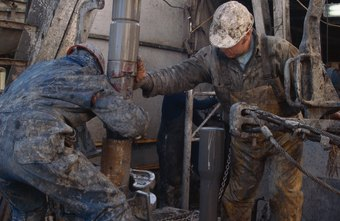 Oil roustabouts maintain oil field pumps.