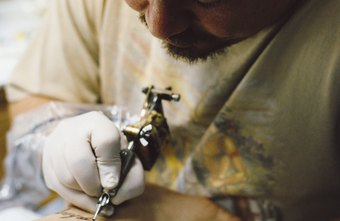 A tattoo artist must work carefully to avoid sticking himself with a tattoo needle.