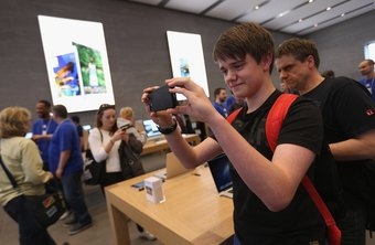 Teen takes photo on iPhone at an Apple store in Berlin
