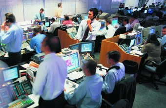 Professional day traders work in large trading rooms with information screens on their desks.
