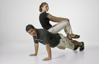 Perform a plank in a pushup position, adding resistance with a partner.