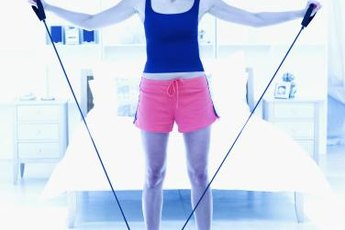 Use a resistance band to warm up your shoulders before playing tennis.