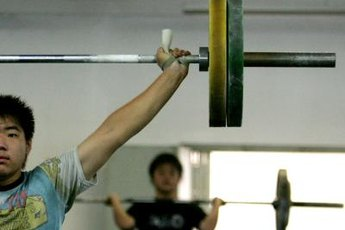 The overhead press is part of a CrossFit Total workout.