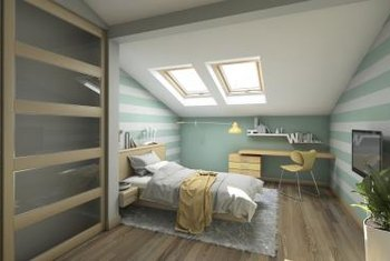 Skylights, horizontal wall stripes and minimal furnishings make an attic bedroom feel and look larger.