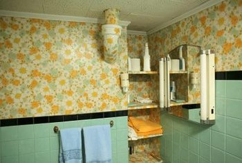 Painting over hard-to-remove bathroom wallpaper may prevent damage to the walls.