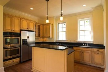 Creamy yellow walls blend with maple cabinets, black granite counters and medium-toned floors.