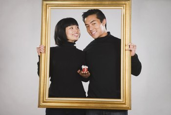 Wood picture frames encircling a picture of the couple sharing the bedroom are regarded as good feng shui.