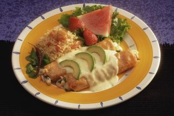 Seafood enchiladas in corn tortillas and Spanish rice make for a healthy Mexican meal, although the cheese sauce adds fat and calories.