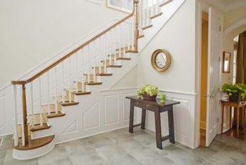 Strengthen a stair railing by tightening the newel post at the bottom of the stairs.