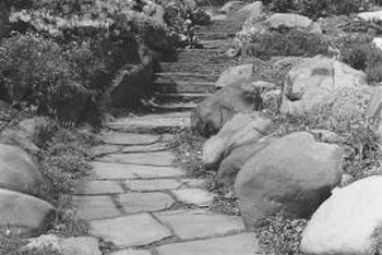 A limestone pathway lined with larger boulders draws the eye through this outdoor space.