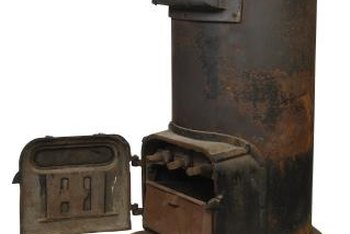 Top a rusty, antique stove with flowering plants for nostalgic decor in the yard.