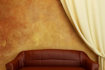 A cream-colored curtain and gold wall make a classic backdrop for this burgundy-tinted brown sofa.