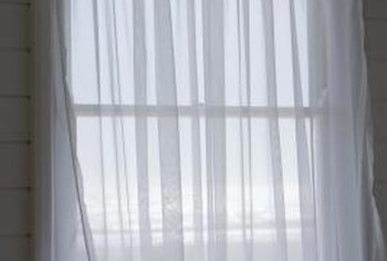 Sheer curtains filter the light in a room.