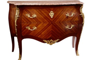 Matched veneer patterns and stamped brass ornamentation suggest a Biedermeier influence.