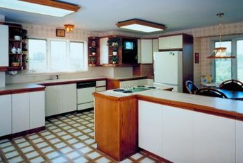 Outdated vinyl flooring that is still in good condition can be covered with stick-on tiles.