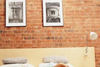 Light-colored furniture and accessories make a small room with a brick wall feel larger.
