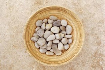 Small, flat pebbles serve as pathway material for a fairy garden.