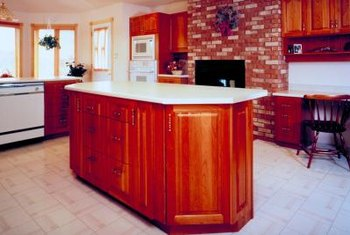 Painting your other kitchen walls in a light shade helps showcase the warm red tones of the brick.
