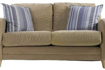 A Khaki Sofa Is Accented By Striped Denim Pillows