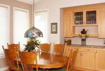 A medium-beige accent wall complements the undertones of the cabinets and dining set.
