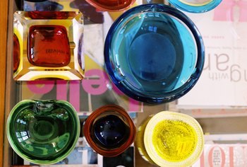 Arrange a collection of colorful glassware on a glass coffee table.