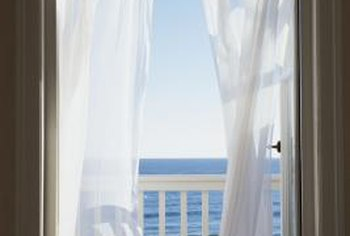 Billowing white balcony curtains create a tropical look.