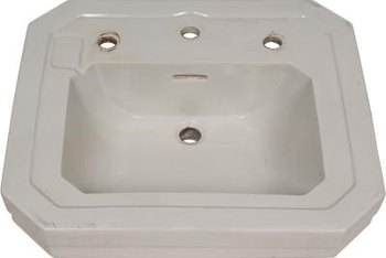 A typical wall-mounted sink has holes for the spout and hot and cold water faucets.