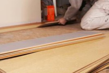 Get a laminate floor under a threshold by removing the threshold.