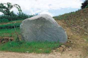 Boulders are naturally occurring in the ground or placed as landscaping.