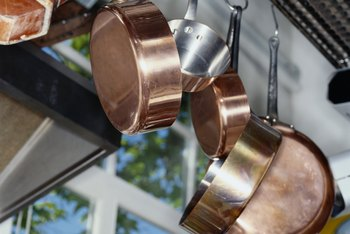 Display shiny copper pans on a ceiling-mounted rack.