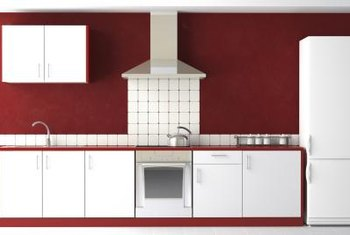 White cabinets provide dramatic contrast against burgundy walls.