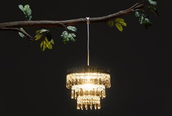 A chandelier hung from a tree branch sets the tone for an elegant outdoor party.