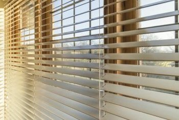 Gleaming horizontal wood blinds run across a bank of windows.