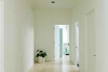 White doors disappear into white walls, leaving an uncluttered vista in a modern space.