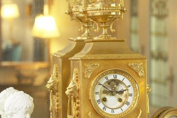 Paintings framed in gold provide a visual link with a gold mantel clock.