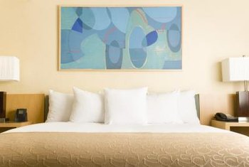 Hanging artwork that contrasts with your bedding above your headboard creates a striking look.