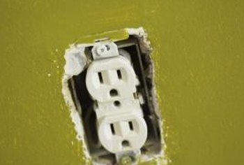 Cut an outlet hole before the drywall is in place.