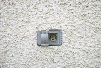 You need access from the other side of the wall to install a flush-mount outlet box in stucco.