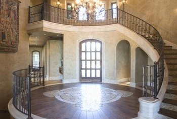 A domed and painted ceiling enhances a dramatic sweeping staircase.