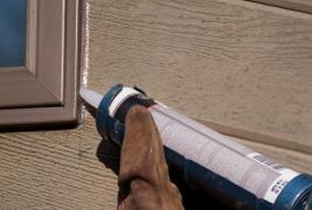 Caulk seals gaps between a window frame and the exterior of a house.