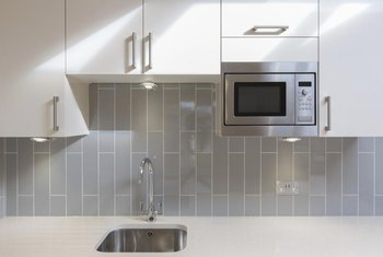 White cabinets enhance the color neutrality of gray tiles.