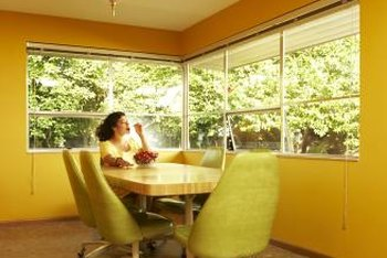 Here is a room with warm-toned, orange-yellow walls and cool-toned, green-yellow chairs.