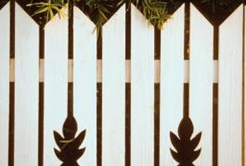 Installing a decorative fence directly in front of your neighbor's concrete wall can easily hide it from view.