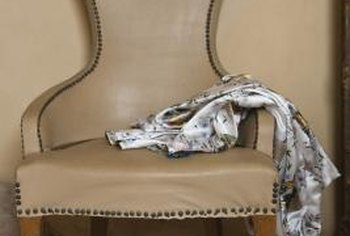 Remove decorative upholstery tacks before stripping away the old fabric or leather.