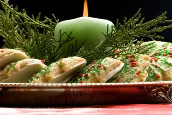 A candle or candles with seasonal decor serve as a table centerpiece.