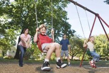 A layer of wood chips makes a softer landing area for a swing set.