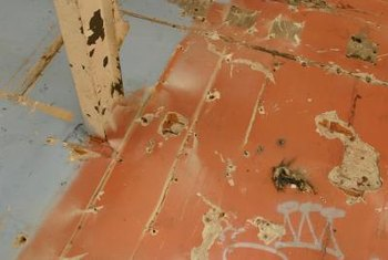 Prepping plywood flooring for refinishing often involves removing old glue.