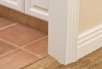 Cutting the bottom of the door trim allows the tile to slide under it easily.