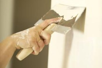 Hold the trowel or drywall finishing knife at a slight angle to apply repair compound.