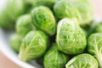 Brussels sprouts resemble small heads of cabbages with their compact, leafy layers.